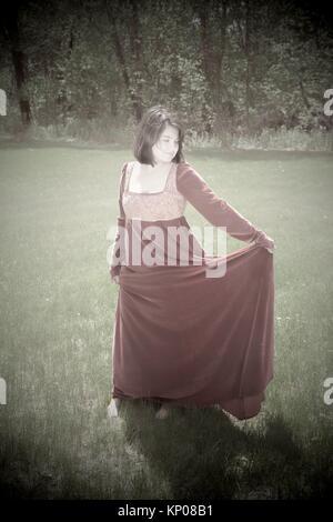 Junge Frau, die in einem Park, trug einen langen roten vintage Kleid. - Stockfoto