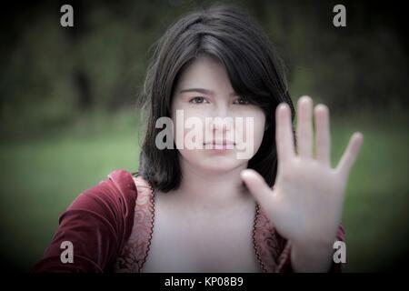 Junge Frau, ihre Hand erweitert und stehen in einem Park, trug einen roten vintage Kleid. - Stockfoto