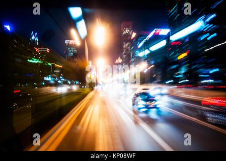 Verschwommen Ampel Spuren auf der Straße in der Nacht in China. - Stockfoto