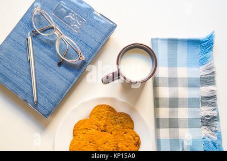 Notiz Buch, Brillen, Kugelschreiber, Schüssel, Cookies, Tasse Milch und Serviette. - Stockfoto