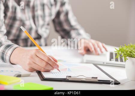 Geschäftsmann mit einem Stift wird die Arbeit mit Graphen Dokumente. Börse chart und Schuldzuweisungen auf Tablet - Stockfoto