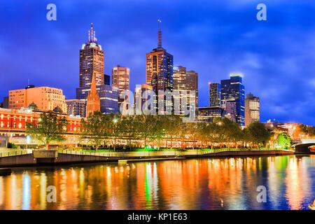 Blaue Dunkelheit über die Stadt Melbourne CBD überragt Flinders Bahnhof mit heller Beleuchtung in unscharfer Gewässern des Yarra River spiegeln.