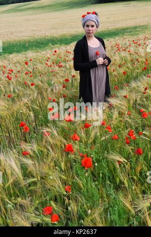 Junge Frau in einem Müsli Feld bestreut mit Mohn, Frankreich, Europa. - Stockfoto