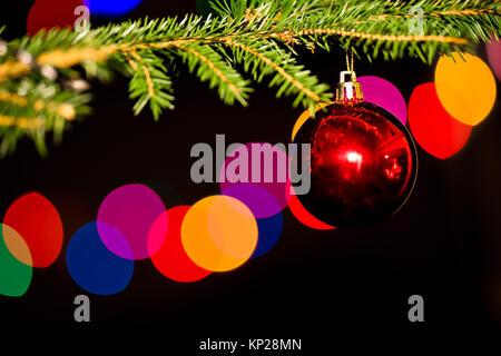 Eine rote Christbaumkugel auf dem Weihnachtsbaum, ein Kamin Reflexion in der christbaumkugel - Stockfoto