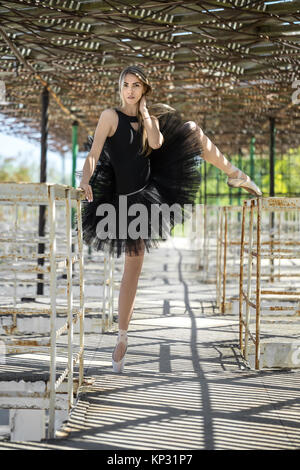 Bezaubernde Ballerina mit geöffneten Lippen in einem schwarzen Tutu steht auf dem rechten Bein auf der Betonpfeiler - Stockfoto