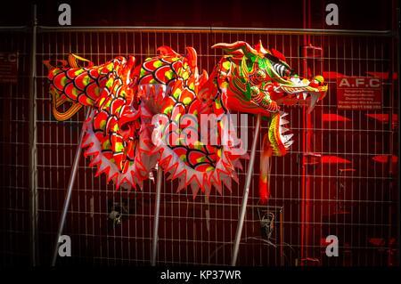 Ein chinesischer Drache lieas ruhenden gegen einen Zaun - wartet auf die Betreiber, die Kontrolle zu übernehmen - Stockfoto
