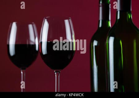 In der Nähe von Wein Gläser und Flaschen gegen roter Hintergrund - Stockfoto