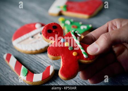 Nahaufnahme eines jungen kaukasischen Mann mit einem handgefertigten Weihnachtsplätzchen in der Form eines Gingerbread - Stockfoto