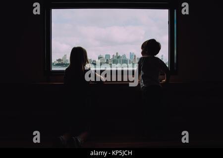 Bruder und Schwester Geschwister mit Blick auf die Skyline der Stadt vom grossen Fenster - Stockfoto