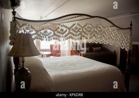 Old Fashion weiß gestrickt, sehr niedrige Bett Möbel in einem Hotel an der Küste in den Outerbanks von North Carolina. - Stockfoto