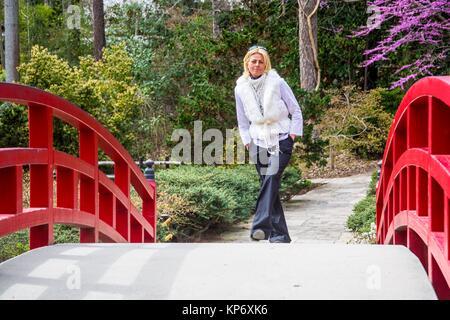 Schöne blonde Frau, gekleidet in Weiße und Schwarze gehen auf eine rote Brücke in botanischen Gärten. - Stockfoto