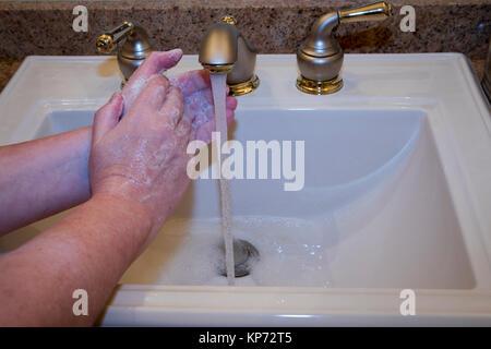 Nahaufnahme von Frau Waschen der Hände im Waschbecken im Bad. - Stockfoto