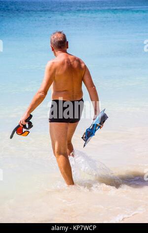 Ältere fällige Senior kaukasischen Rentnerehepaar an den Strand gehen und Duschen nach dem Schwimmen. Sie sehen - Stockfoto