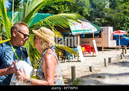 Zu Fuß rund um den Strand Les Salines in Martinique. Rentnerehepaar senior Küssen und zusammen spielen Sie all die - Stockfoto