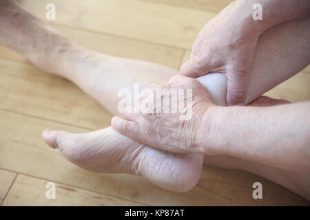 Sitzt der Mensch seine schmerzhaften Knöchel Holding - Stockfoto