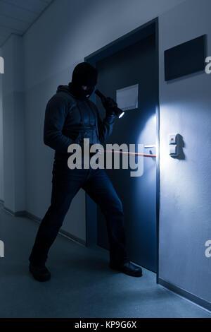 Dieb mit Taschenlampe Versuchen zu brechen Büro Tür - Stockfoto