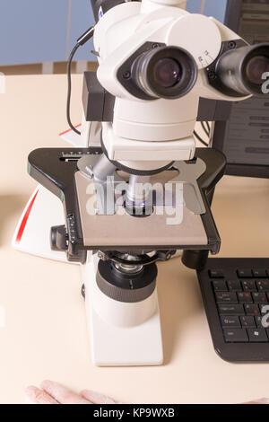 Medizinische oder wissenschaftliche Forscher unter Verwendung eines Mikroskops in Laborumgebung mit Reagenzgläsern - Stockfoto