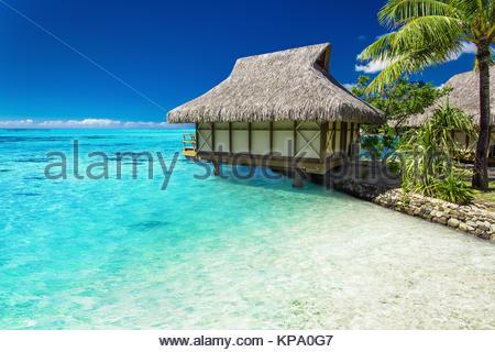 Tropischer Bungalow und Palm-Baum neben erstaunlich blauen Lagune - Stockfoto