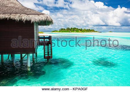 Over Water Bungalow mit Schritten in erstaunliche Blaue Lagune mit der Insel - Stockfoto