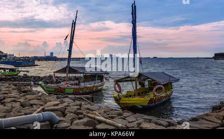 Jakarta, Indonesien - 16. März 2016: Boote am Ufer, farbenfrohen Sonnenuntergang über der Skyline von Jakarta, Java, - Stockfoto