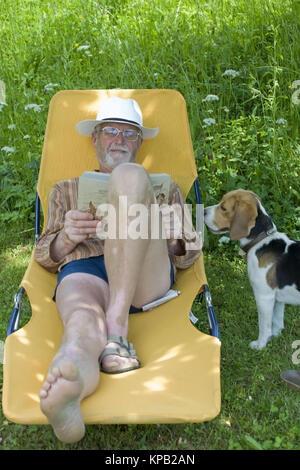 Model Release, Pensionist, 65 +, so Auf Liegestuhl Im Garten Und liest Ein Buch, Lebenswege Steht Sein Hund - Rentner - Stockfoto