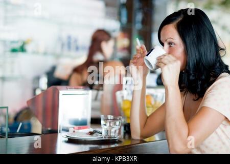 Model Release, Junge Frau Sitzt Mit Kaffee Und Zigarette Im Kaffeehaus - junge Frau trinkt Kaffee und raucht Zigarette - Stockfoto