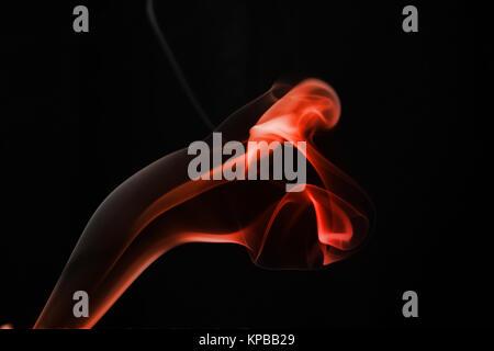 Eine whisp der roten Rauch gegen den schwarzen Hintergrund - Stockfoto