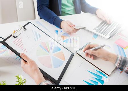 Geschäftsleute über die Tabellen und Grafiken zeigen die Ergebnisse ihrer erfolgreichen Teamarbeit. Börse chart - Stockfoto