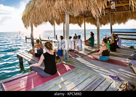 CAYE CAULKER, Belize - 17.12.2015: Yoga am Dock von Caye Caulker Insel am 17.Dezember 2015, Belize. Die Teilnehmer - Stockfoto