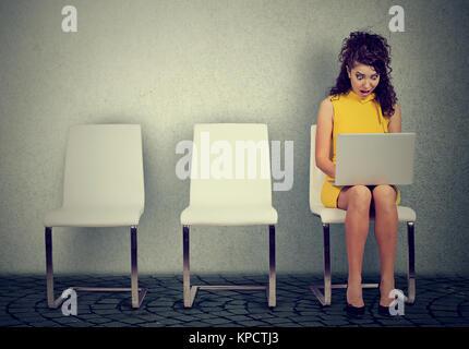 Junge Frau sitzt auf einem Stuhl und surfen Laptop mit Ausdruck der Bestürzung. - Stockfoto