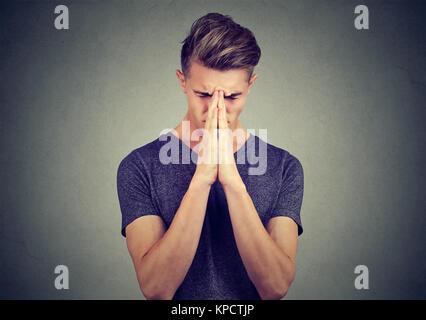 Junger Mann Hand in Hand zusammen und berühren die Stirn beten mit starken Gefühlen halten die Augen geschlossen. - Stockfoto