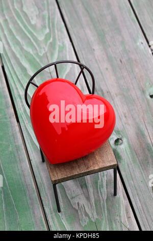 Herz auf kleines Spielzeug Stuhl, Grunge Holz Hintergrund - Stockfoto