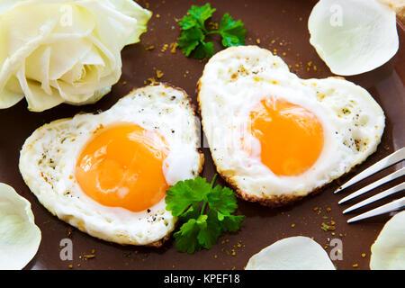 Zwei herzförmigen Spiegeleier auf einem Teller. Valentinstag Frühstück. - Stockfoto