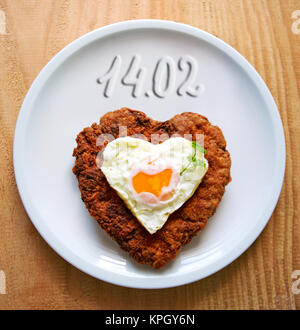 Herzförmige Hackfleisch/Faschiertes Steak mit Spiegelei auf weiße Platte. Valentinstag. - Stockfoto