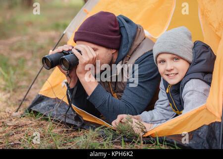 Vater und Sohn mit dem Fernglas im Zelt - Stockfoto