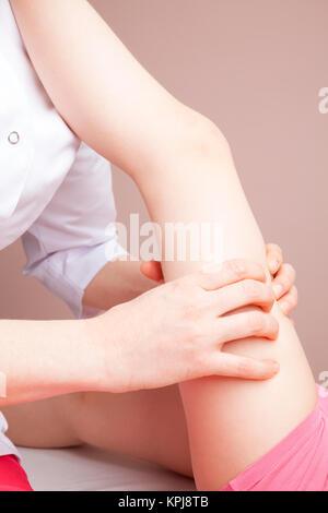Die elementare Alter Mädchen Oberschenkel durch ein osteopath - eine alternative Medizin Behandlung manipuliert - Stockfoto