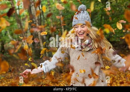 Frau spielen in Blätter im Herbst. - Stockfoto