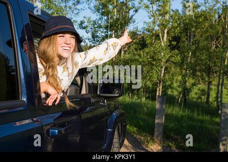 Junge Frau mit Hut Neigung des Fahrzeugs öffnen Fenster mit einem großen Lächeln und den Arm in den Himmel gehoben; - Stockfoto