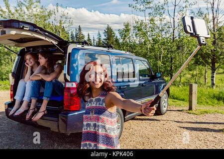 Zwei junge Frauen auf einem Road Trip sitzen in der Rückseite eines Fahrzeugs sprechen und gemeinsam lachen, während - Stockfoto