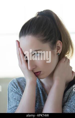 Traurige junge Frau, die Augen mit der Hand in Bedauern - Stockfoto