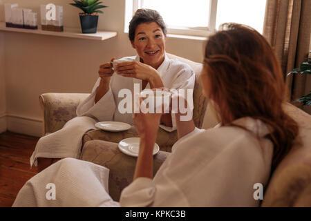 Zwei weibliche Freunde trinken Kräutertee und Chatten in Spa Salon. Frauen Entspannen im Spa Rezeption. - Stockfoto