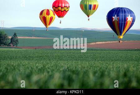 Bunte Heißluftballons schweben über ein Weizenfeld in Walla Walla, Washington - Stockfoto