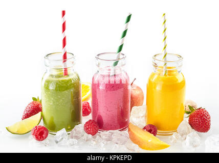 Drei gesunde Smoothies mit frischen tropischen Früchten wie Erdbeere, Himbeere, Orange, Limette, Mango und Apple - Stockfoto