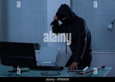 Räuber mit Taschenlampe im Büro - Stockfoto