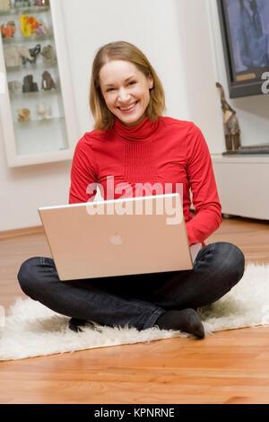 Model Release, Junge Frau Sitzt Mit Laptop im Wohnraum - junge Frau mit laptop - Stockfoto