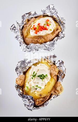 Zwei gegrillte gebackene Kartoffeln in Alufolie gekrönt mit Sauerrahm und mit gehackten Schnittlauch und Pfeffer - Stockfoto
