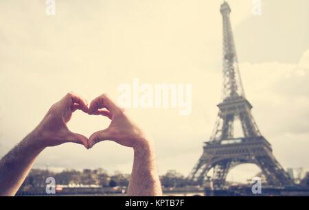Liebe in Paris - die Hände bilden ein Herz Form vor dem Eiffelturm - Stockfoto