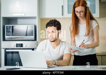 Frau berechnen oder schreiben Sie Konten mit Stift, ihr Mann mit Laptop - Stockfoto
