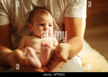 Neugeborenes Baby Beine in Mütter schöne Hand mit weichen Fokus auf und Schuhen Fuß - Stockfoto