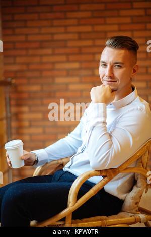 Gut aussehender Geschäftsmann trinken Kaffee im Haus und suchen Kamera - Stockfoto